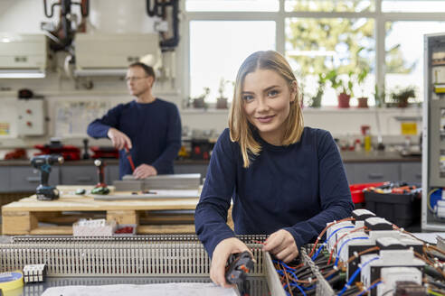 Portrait of smiling female electrician working on circuitry in workshop - ZEDF03226