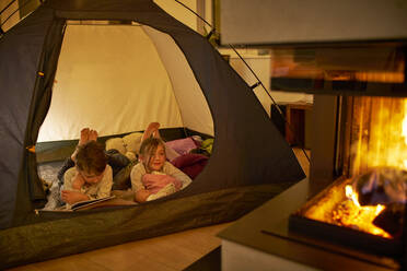 Brother and sister camping in the living room near fire place - DIKF00458