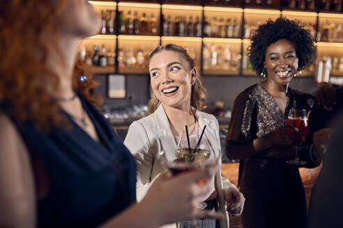 Happy friends socializing in a bar - ZEDF03279