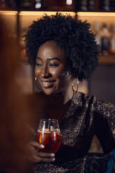 Portrait of woman having a cocktail in a bar - ZEDF03282