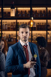 Portrait of a serious young man having a cocktail in a bar - ZEDF03288