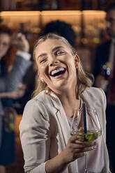 Portrait of a happy young woman having a cocktail in a bar - ZEDF03294
