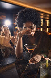 Cheerful woman having a cocktail in a bar - ZEDF03309