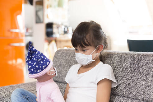 Little girl with protective mask sitting on couch at home playing with doll - DRF01759