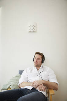 Man listening to music with headphones at home - FSF01025