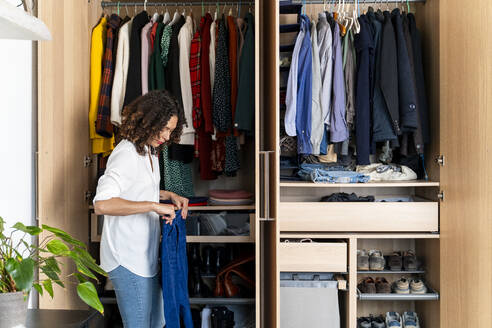 Woman clearing out her wardrobe - FMOF00971