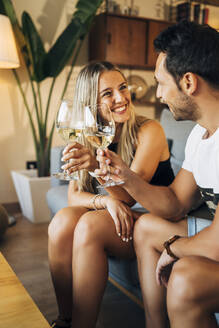 Happy couple sitting on the couch toasting with glasses of white wine - MPPF00798
