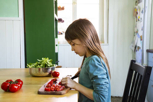 Girl cutting tomatoes on chopping board in kitchen - LVF08808
