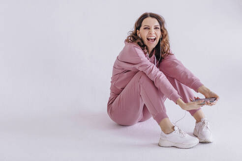 Brunette woman wearing pink track suit and listening to music, holding smartphone - OGF00293