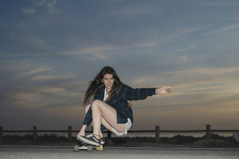 Young woman skateboarding on asphalt road at dusk, Almeria, Spain - MPPF00833