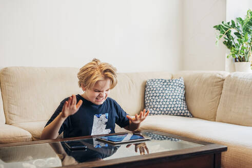 Frustrated boy with smartphone and tablet in living room - MJF02460