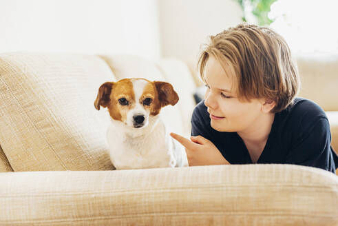 Boy with dog lying on couch in living room at home - MJF02469