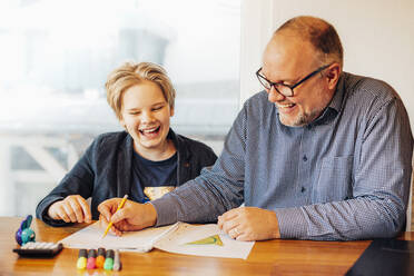 Happy father and son doing homework at desk - MJF02496