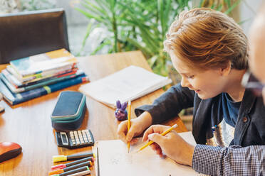 Father helping son doing homework at desk - MJF02499