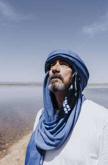 Man in the desert of Merzouga standing in front of lake, Morocco - DAMF00343