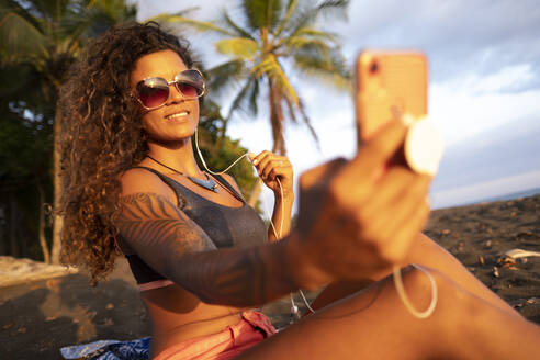 Beautiful woman taking a selfie on the beach, Costa Rica - AMUF00049