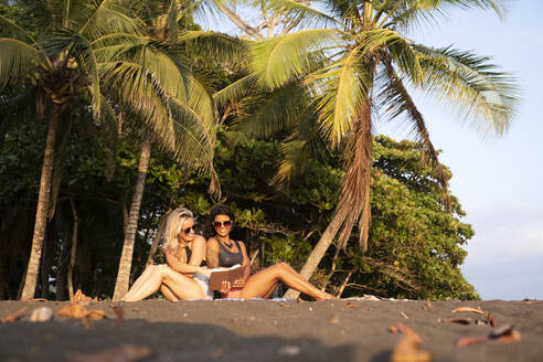 Two women reading a book on the beach, Costa Rica - AMUF00076