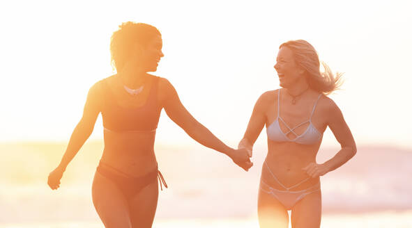 Two carefree women on the beach at sunset, Costa Rica - AMUF00085