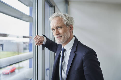 Portrait of confident businessman looking out of window - RORF02126
