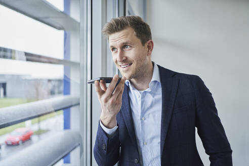 Businessman using cell phone at the window - RORF02138