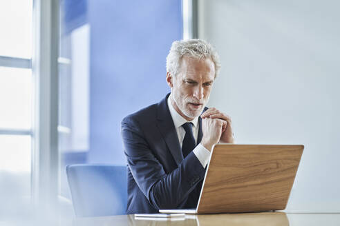 Focused businessman using laptop at desk in office - RORF02150