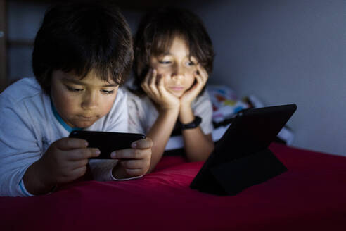 Two brothers lying together on bed at home using electronic devices - VABF02781