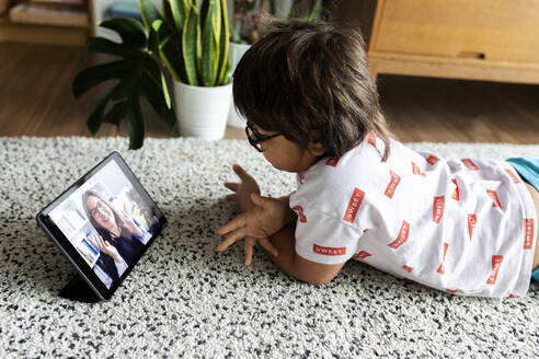 Boy lying on the floor at home using digital tablet for video chat with his mother - VABF02805