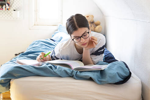 Girl lying on bed doing homework - LVF08817
