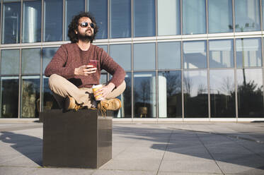 Portrait of bearded man sitting outdoors with coffee to go and smartphone enjoying sunlight - KIJF02972