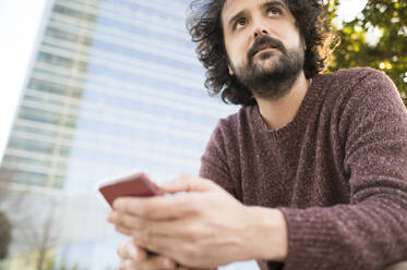 Portrait of bearded man with smartphone outdoors - KIJF02975