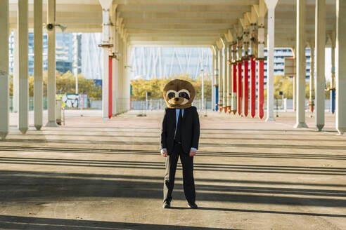 Businessman in black suit with meerkat mask outdoors, Barcelona, Spain - XLGF00027