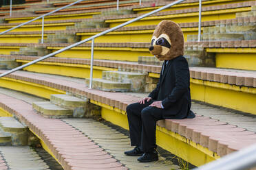 Businessman in black suit with meerkat mask sitting alone on stairs - XLGF00033