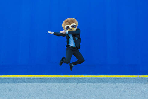 Businessman in black suit with meerkat mask jumping in the air in front of blue wall - XLGF00039