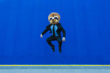 Businessman in black suit with meerkat mask jumping in the air in front of blue wall - XLGF00042