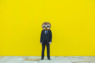 Businessman in black suit with meerkat mask standing in front of yellow wall - XLGF00045