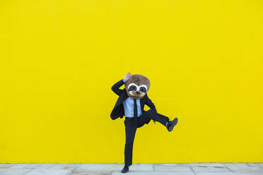 Businessman in black suit with meerkat mask dancing in front of yellow wall - XLGF00048