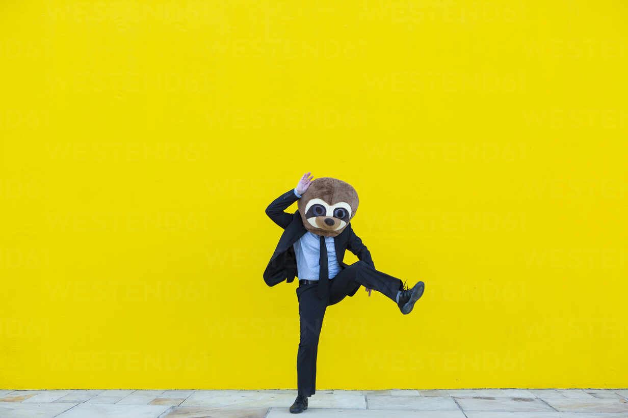 Businessman in black suit with meerkat mask dancing in front of yellow wall - XLGF00048 - Xavier Lorenzo/Westend61