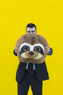 Businessman in black suit with meerkat mask in front of yellow wall - XLGF00051