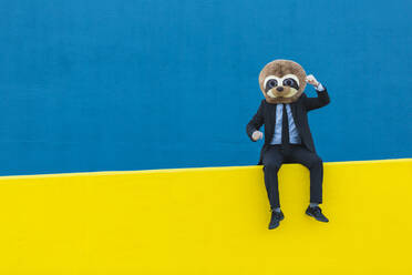Portrait of businessman in black suit with meerkat mask sitting on yellow wall in front of blue background - XLGF00060