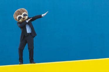 Portrait of businessman in black suit with meerkat mask standing on yellow wall in front of blue background - XLGF00063