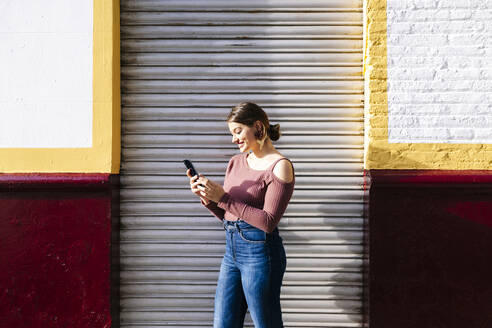 Happy woman using smartphone at a building in the city - DGOF00812