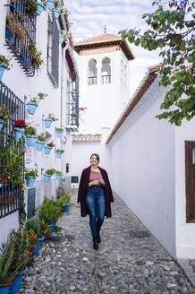 Woman walking in an alley in Albaicin, Granada, Spain - DGOF00836