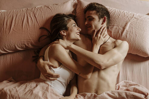 Happy young couple lying in bed - GMLF00037