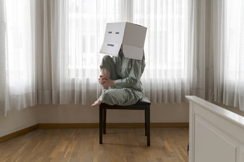 Woman wearing a cardbox on head with bored smiley sitting on chair - AFVF06060