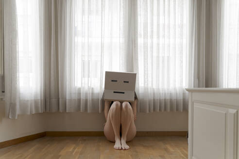 Woman wearing a cardbox on head with bored smiley and sitting on floor - AFVF06063