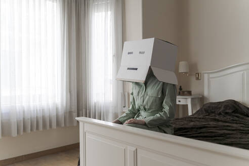 Woman wearing a cardbox on head with bored smiley sitting on bed - AFVF06069