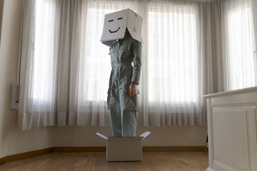 Woman wearing a cardbox on head with bored smiley and standing in box - AFVF06072