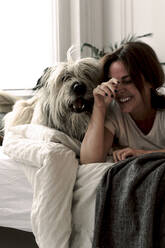 Laughing mature woman lying on bed playing with her dog - ERRF03483