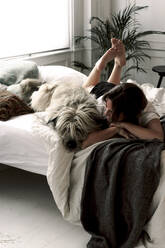 Mature woman lying on bed with her dog relaxing - ERRF03486
