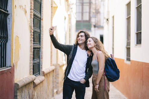Smiling young couple taking selfie while standing on narrow street at Santa Cruz, Seville, Spain - DGOF00867